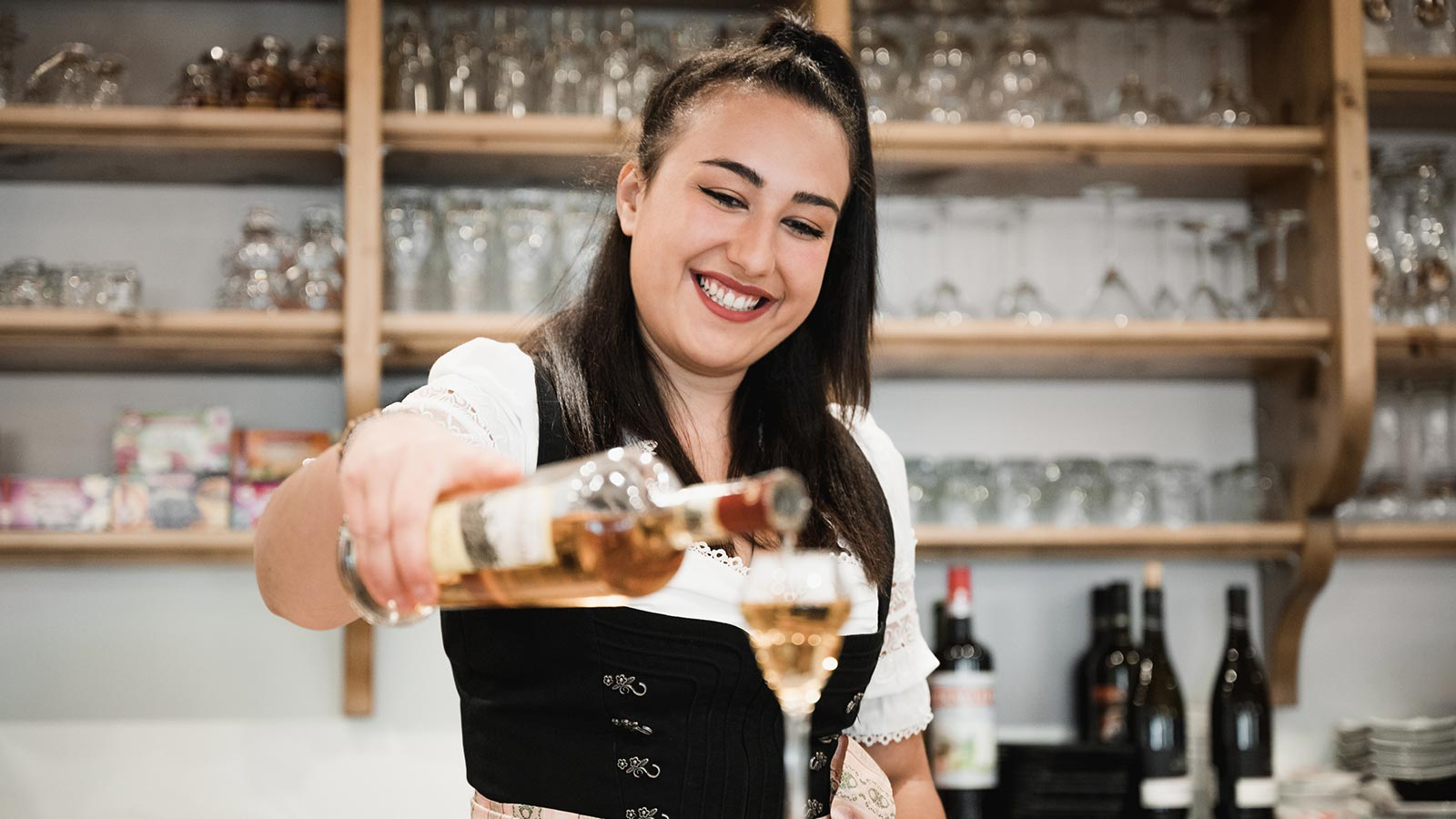 A bartender in traditional dress pours a glass of grappa at the bar counter