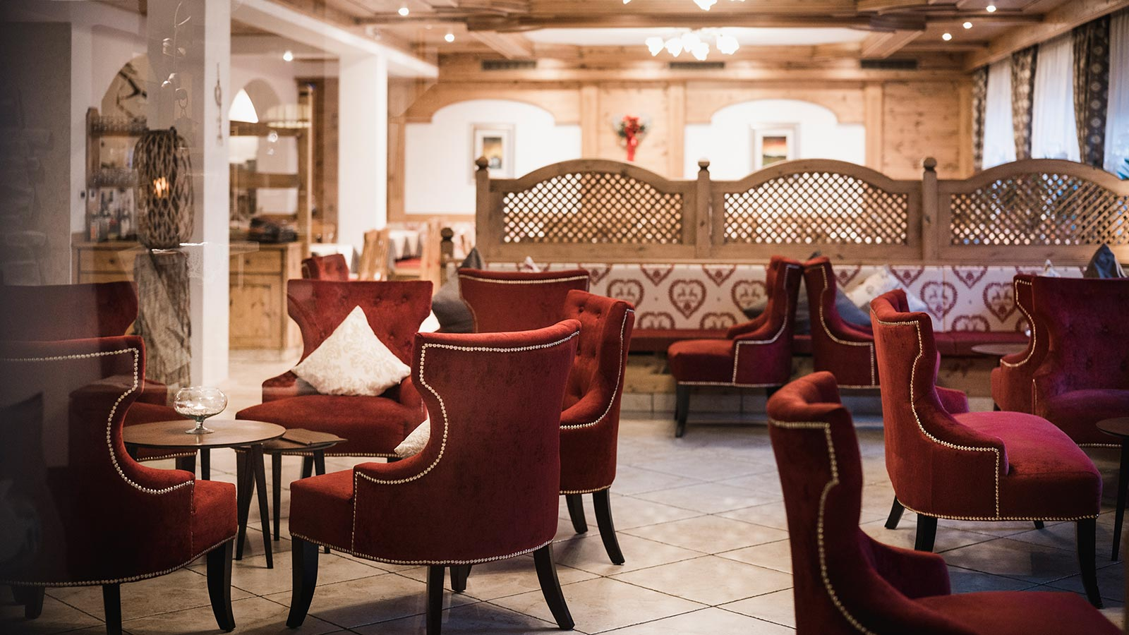 The bar of the Hotel Laguscei with red velvet armchairs and wooden walls