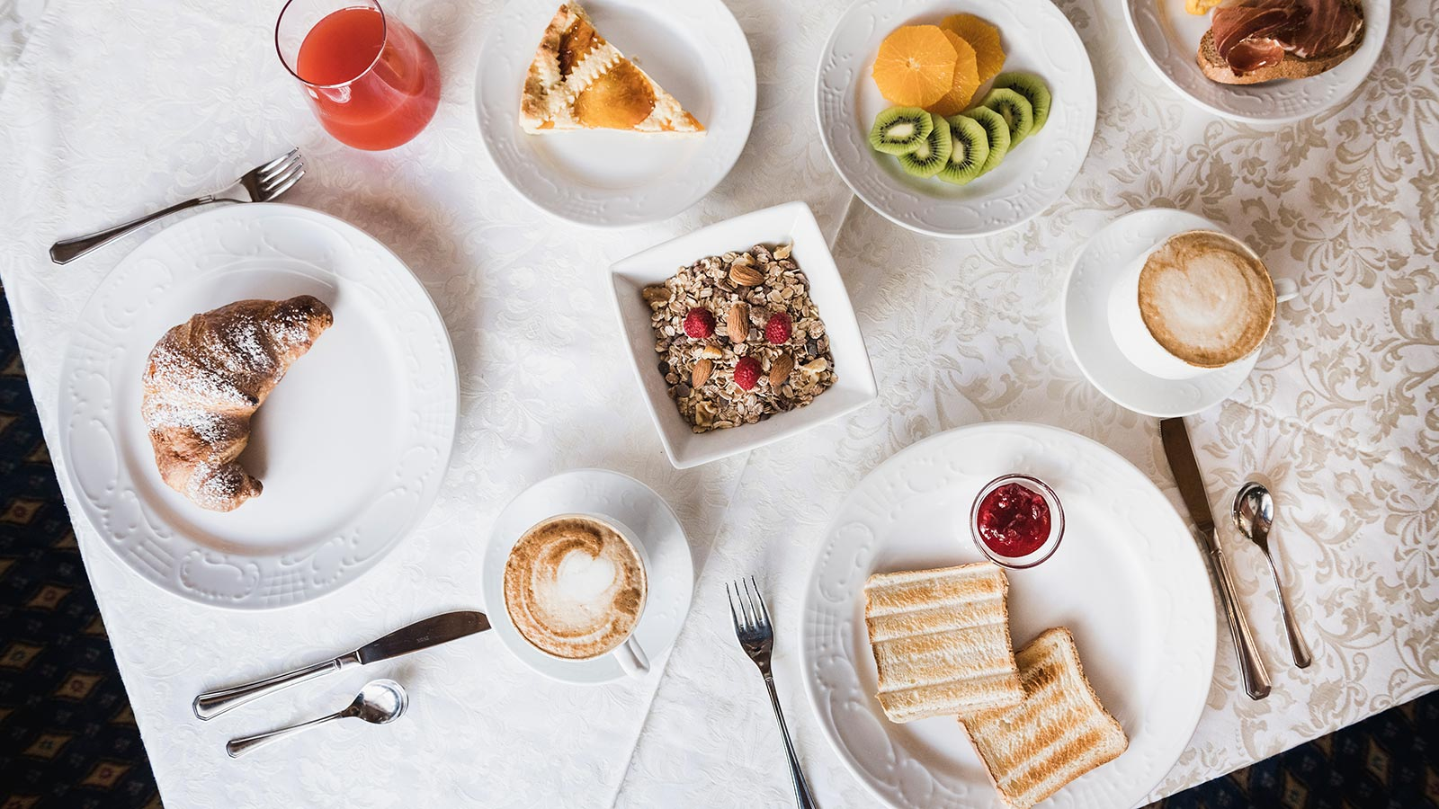 A tasty breakfast with fruit, croissants, muesli, tarts and cappuccino at the Hotel Laguscei