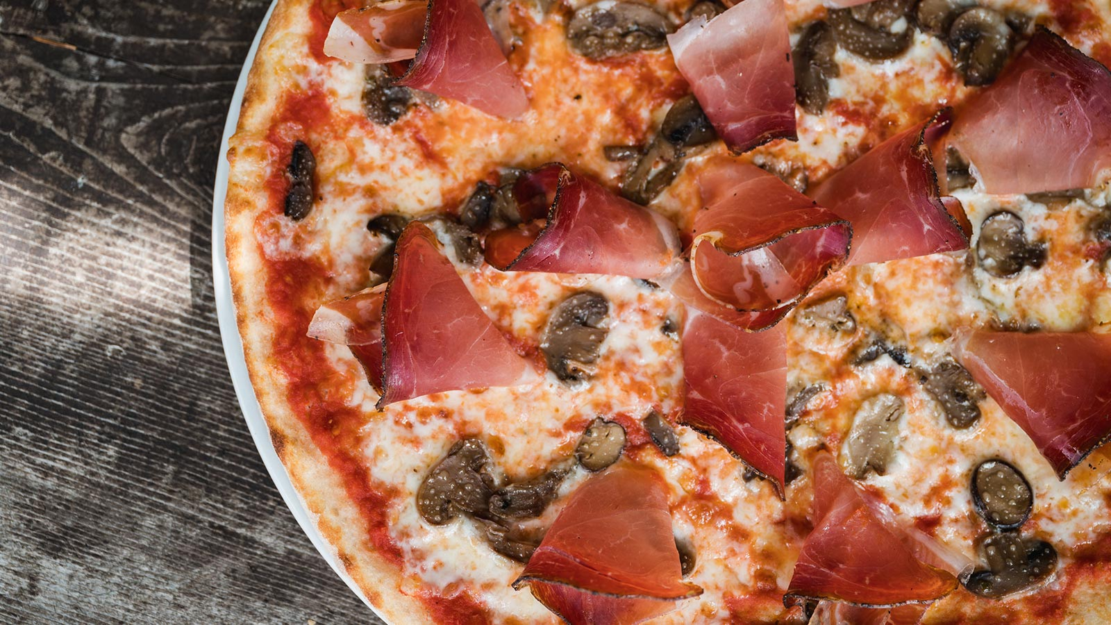 A tasty pizza with mushrooms and speck at the restaurant in Arabba