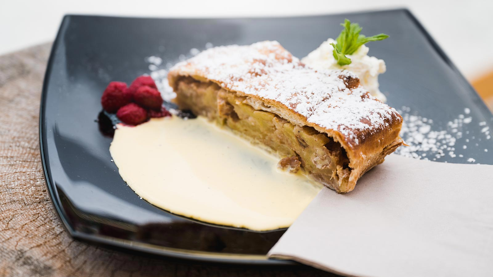 A slice of strudel with vanilla sauce and some raspberries at the restaurant in Passo Campolongo