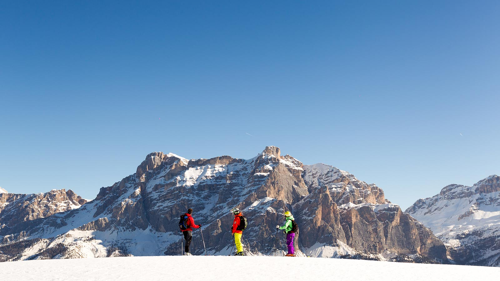 Three skiers admire the Dolomites on a sunny winter day