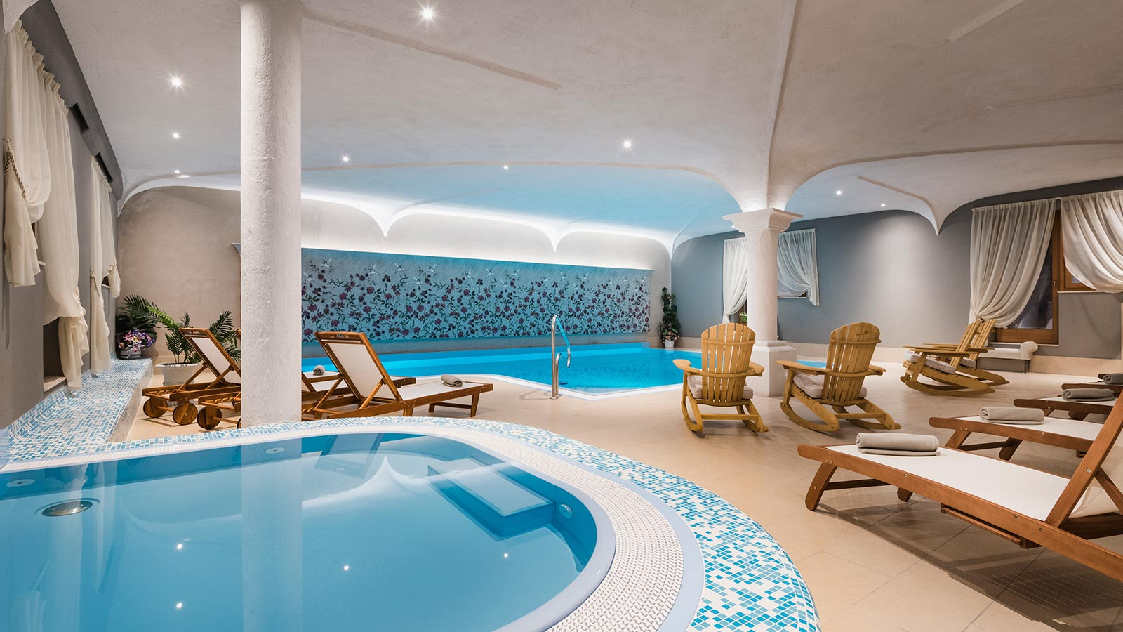 The indoor swimming pool with deckchairs and sunbeds of our wellness hotel in the Dolomites