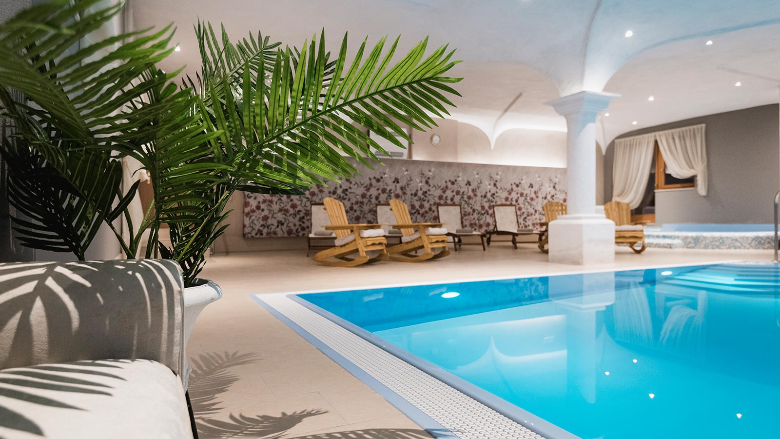 The indoor swimming pool with a palm tree and some deckchairs